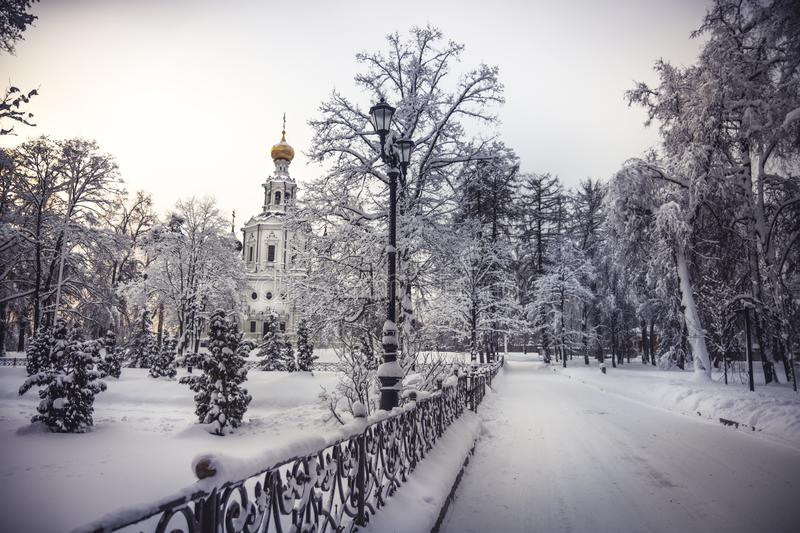 Orthodox Christian church in winter snowy park during winter season with snowy covered trees and way alley leading to church stock photo