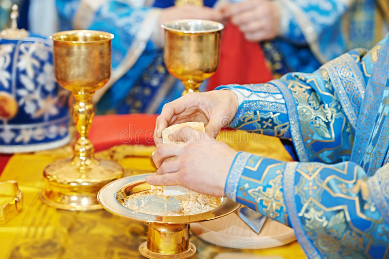 Orthodox Christian euharist sacrament ceremony. Christian sacrament. Hands of priest refracting bread during orthodox liturgy ceremony royalty free stock photos
