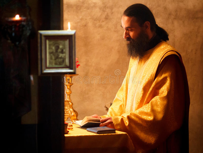 Orthodox christian priest monk during a prayer praying portrait. In church monastery in Serbia stock image