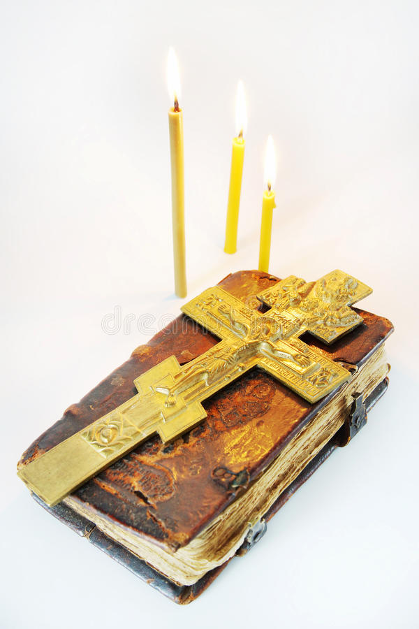 Orthodox Christian still life with crucifixion over ancient book. Orthodox Christian still life with a metal crucifixion over ancient book on light background royalty free stock photos