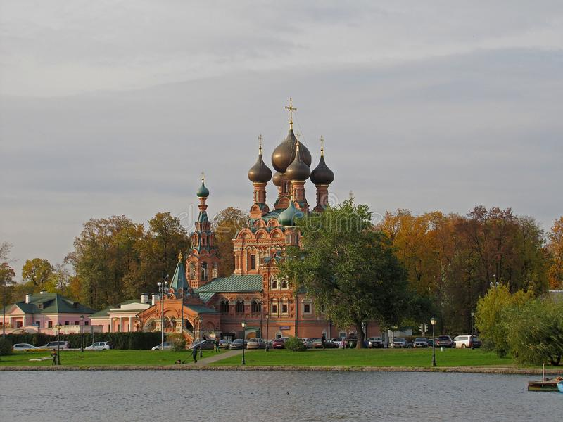 Orthodox church on the bank of a pond in Moscow in early autumn stock images
