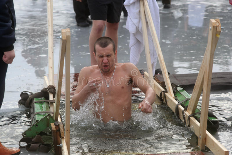 Orthodox church Holy Epiphany Day. Weather -15. DAUGAVPILS, LATVIA - January 19, 2015: Orthodox church Holy Epiphany Day. Weather -15. People bathed in the ice stock photography