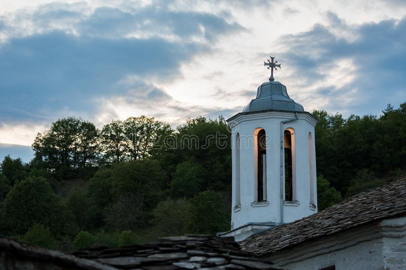 Orthodox church lit dome with cross at evening. Lit dome of orthodox church with decorated cross and brass bell at evening, village of Dolen, Rhodope mountain royalty free stock photography