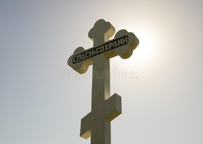 Orthodox cross against the blue sky and the sun. Cross in the ba. Krasnodar, Russia - April 29, 2017: Orthodox cross against the blue sky and the sun. Cross in stock photography
