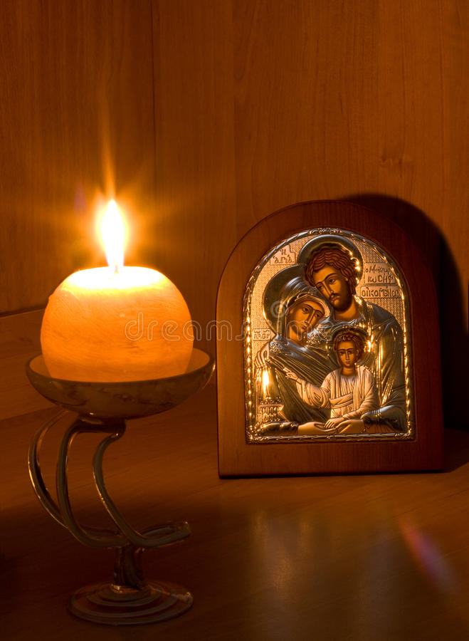 Orthodox Family icon and flaming candle stock images