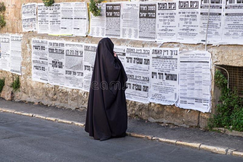 Orthodox jewish `Taliban women` read street poster in jewish quarter. JERUSALEM, ISRAEL - MARCH 31, 2017: Orthodox jewish `Taliban women` read street poster in royalty free stock photos