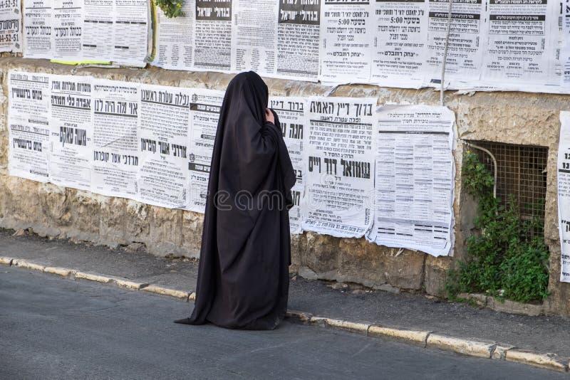 Orthodox jewish `Taliban women` read street poster in jewish quarter. JERUSALEM, ISRAEL - MARCH 31, 2017: Orthodox jewish `Taliban women` read street poster in stock photos