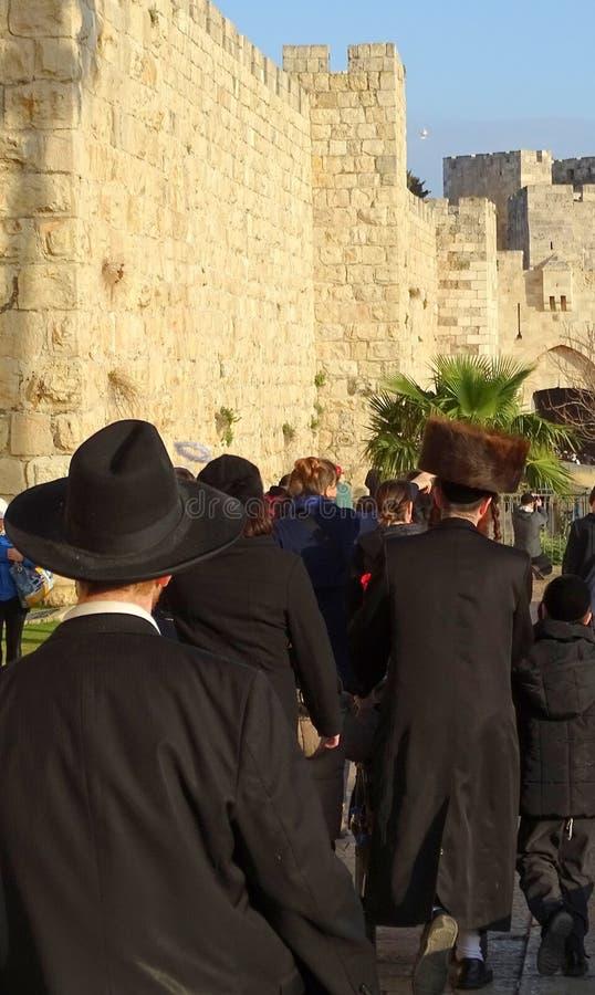 Orthodox Jews walking along the city wall of Jerusalem towards Jaffa Gate stock images