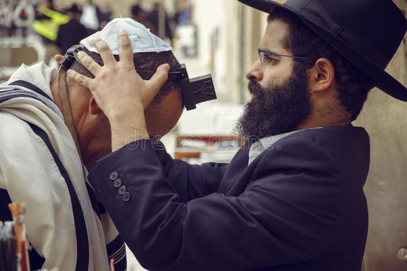An orthodox man putting a Jewish Tefillin on another prayer head royalty free stock images