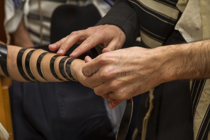 An orthodox man, wearing prayer shawl, put a Jewish Tefillin on A young man arm preparing for a pray, as part of a Jewish ritual royalty free stock photo