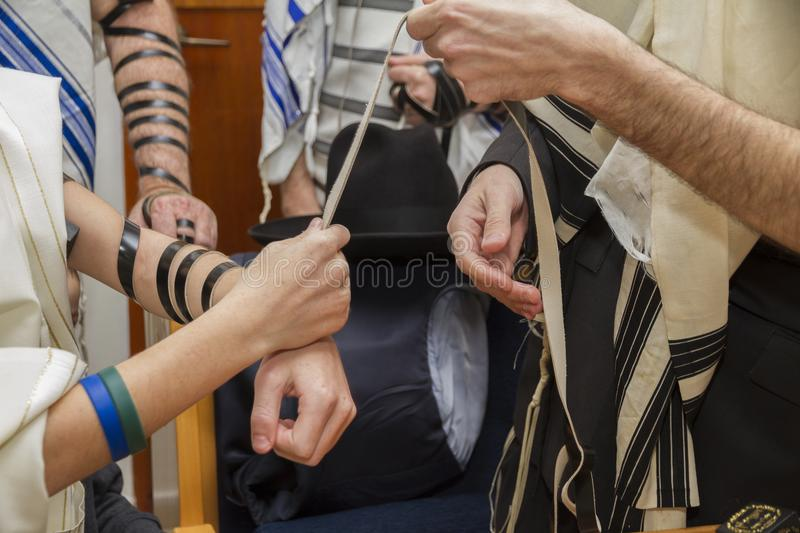 An orthodox man, wearing prayer shawl, put a Jewish Tefillin on A young man arm preparing for a pray, as part of a Jewish ritual royalty free stock image
