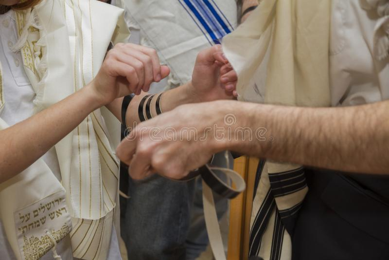 An orthodox man, wearing prayer shawl, put a Jewish Tefillin on A young man arm preparing for a pray stock photography