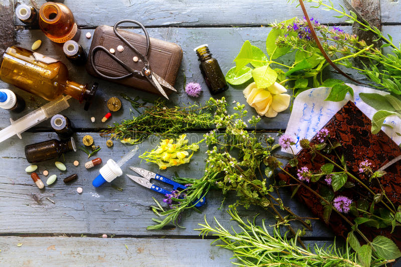 from orthodox medicine to natural medicine, from pills and drops to healing herbs with equipment on a rustic wooden table stock image