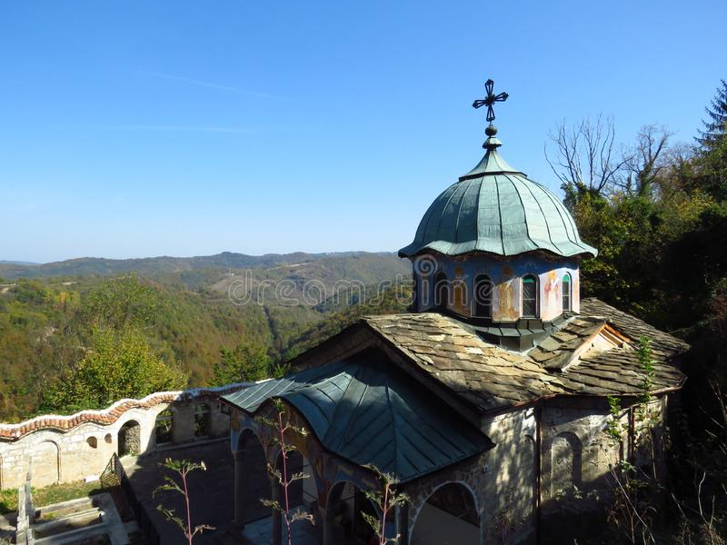 Orthodox monastery dome roof with a metal cross on the top in mountains. Century old monastery church surrounded by trees. Faith, religion, relief, orthodox stock photo