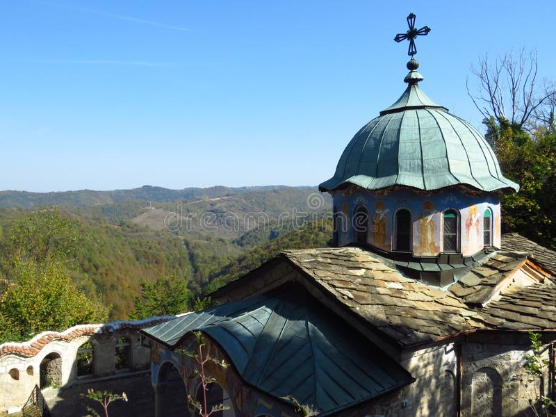 Orthodox monastery dome roof with a metal cross on the top in mountains. Century old monastery church surrounded by trees. Faith, religion, relief, orthodox stock image