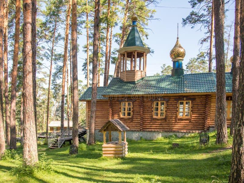 Orthodoxe hölzerne Kirche im Kiefernwald lizenzfreie stockfotografie