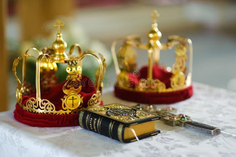 Orthodoxe Hochzeitskronen, -evangelium und -kreuz stockfotos