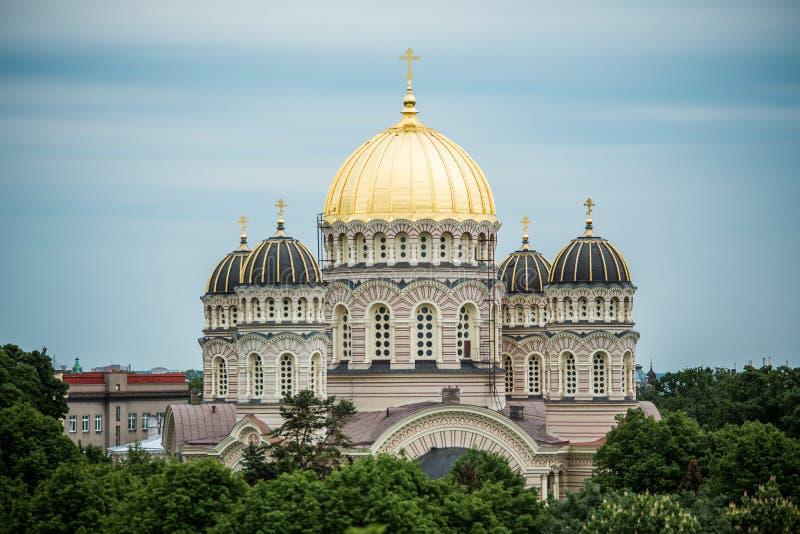 Orthodoxe Kathedraal gouden koepel boven de stadsbomen van Riga stock foto
