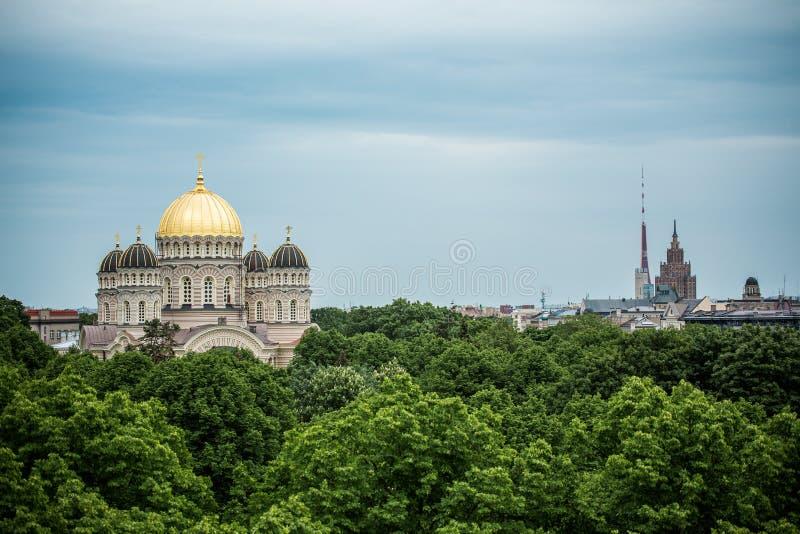Orthodoxe Kathedraal gouden koepel boven de stadsbomen van Riga stock foto's