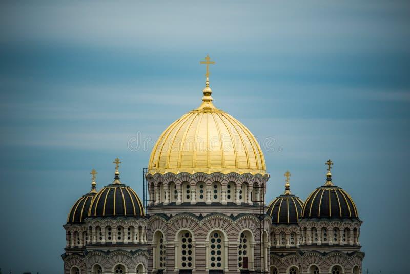 Orthodoxe Kathedraal gouden koepel boven de stadsbomen van Riga royalty-vrije stock fotografie