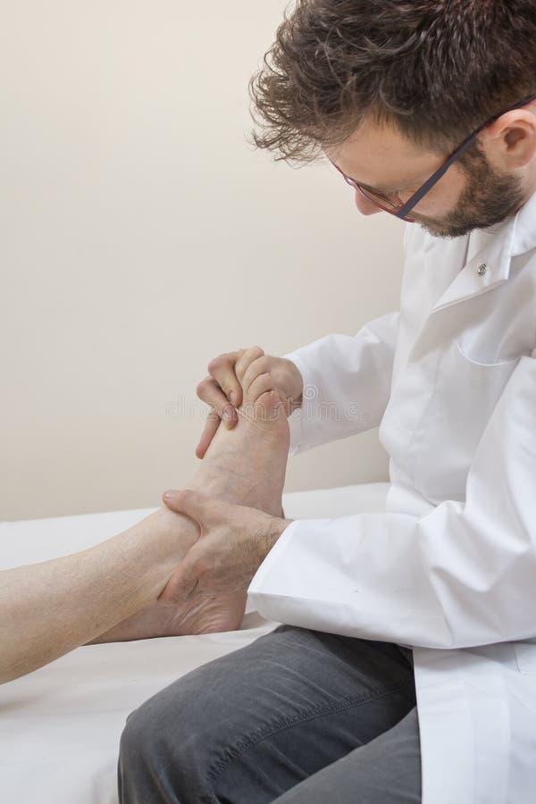 Orthopädedoktor überprüft den Fuß einer alten Frau, die auf einem Bett liegt lizenzfreies stockfoto