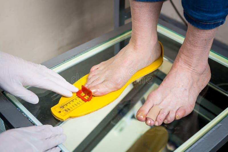 Orthopädie und Medizin Junge kaukasische Doktorhandmanntätowierungslatexhandschuhgrößenmaßform des Fußes für das manufact stockfotografie