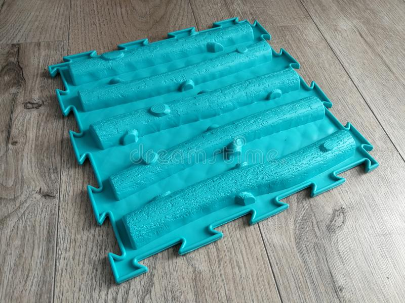 Orthopädische Matte für Fußmassage auf dem Bretterboden stockfotografie