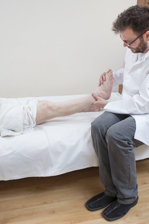 Orthopädischer Doktor überprüft das Bein einer alten Frau lizenzfreies stockbild