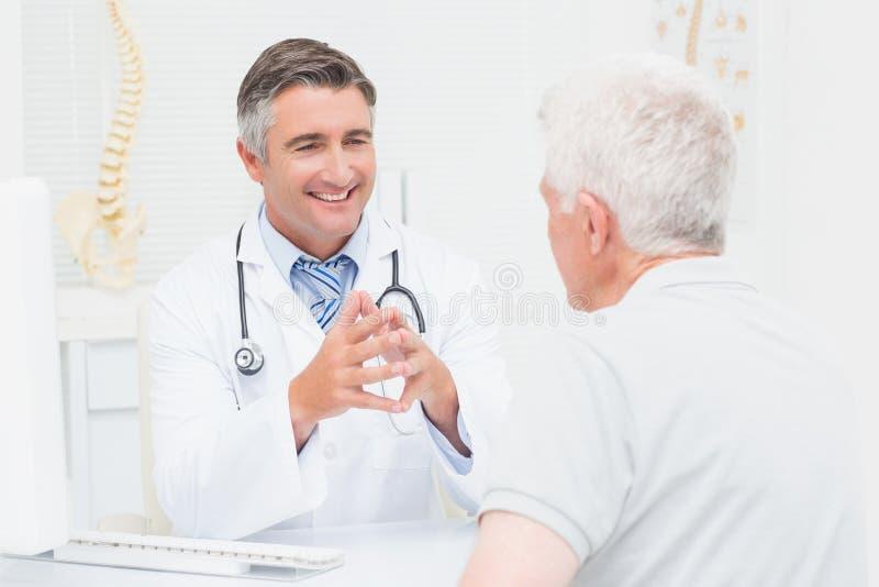 Orthopädischer Doktor, der mit älterem Patienten sich bespricht lizenzfreies stockbild