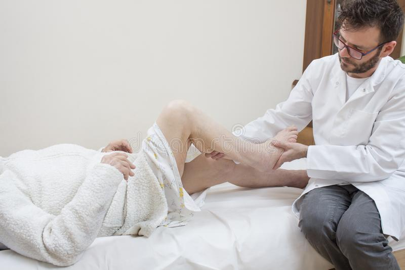 Orthopedic doctor examines the leg of an old woman. royalty free stock images