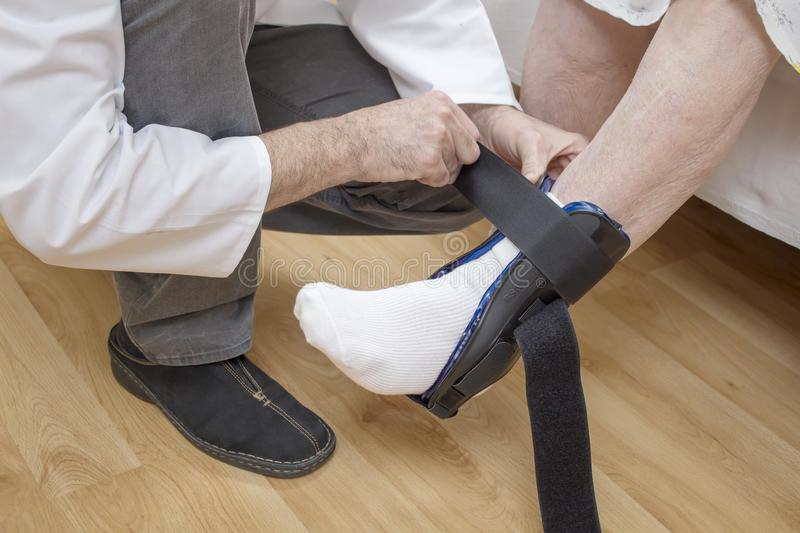 Orthopedic doctor will fasten the ankle stabilizer on the leg of an old woman. stock photography