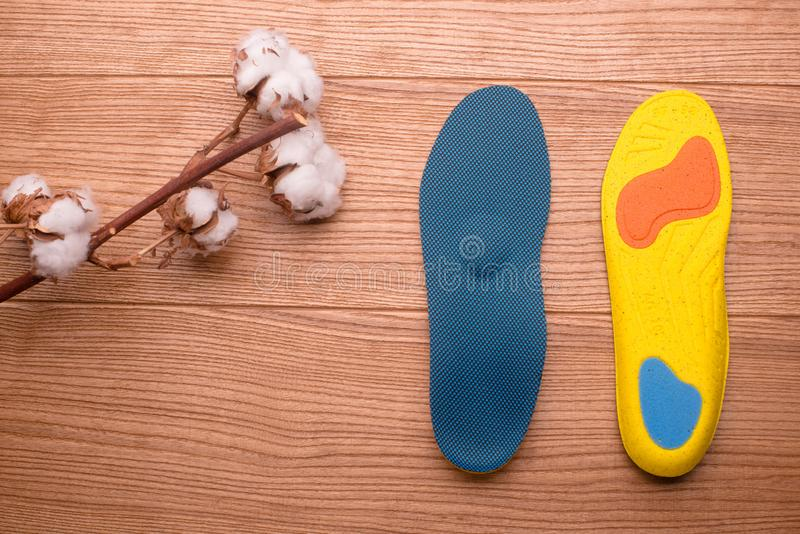 Cotton branch and orthopedic insoles on a wooden table. Orthopedic insoles close-up. insoles with cotton. composition of insoles. natural cotton. cotton flower royalty free stock photography