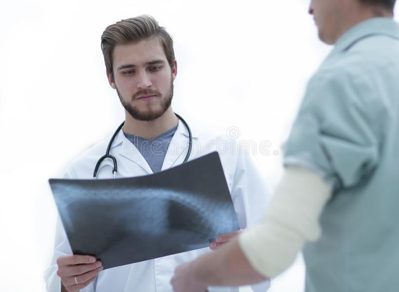 Orthopedic surgeon examining an x-ray of the patient. Standing in hospital corridor stock photography