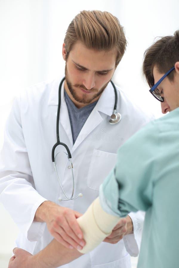 Orthopedist που εφαρμόζει τον επίδεσμο επάνω στον υπομονετικό βραχίονα ` s στοκ φωτογραφία