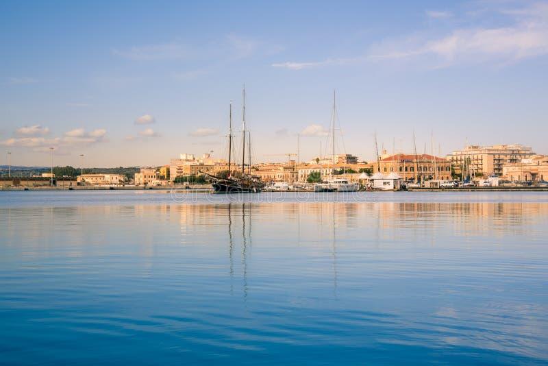 Ortigia,西勒鸠斯,意大利/2018年12月:风船和游艇靠码头在小游艇船坞 绿松石海水,晴朗的天空,浪漫 免版税图库摄影