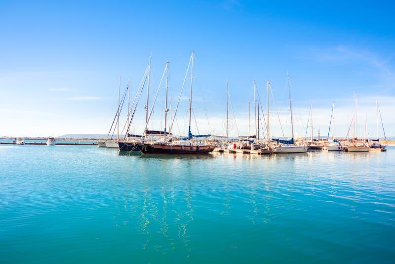 Ortigia, Syracuse, Italy / December 2018: Sailboats and yachts docked at the marina. Turquoise sea water, sunny sky, romantic royalty free stock images