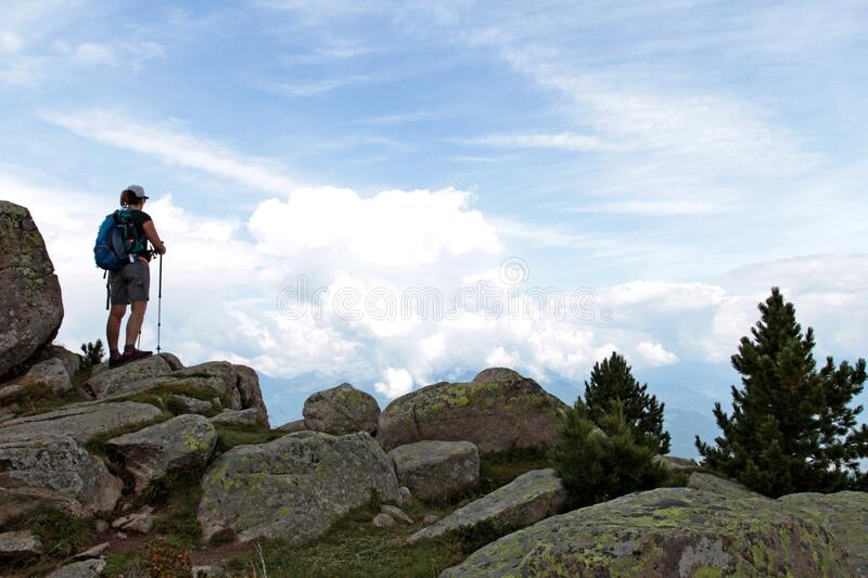 A woman stops at the top of Alpe Rasciesa to admire the view. Ortisei, Trentino-Alto Adige, Italy - August 2019: a woman stops at the top of Alpe Rasciesa to stock photography