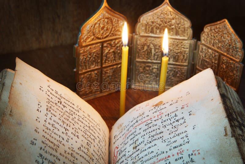 Ortodoksalny religijny życie z otwartą antyczną książką i świeczkami wciąż obrazy stock