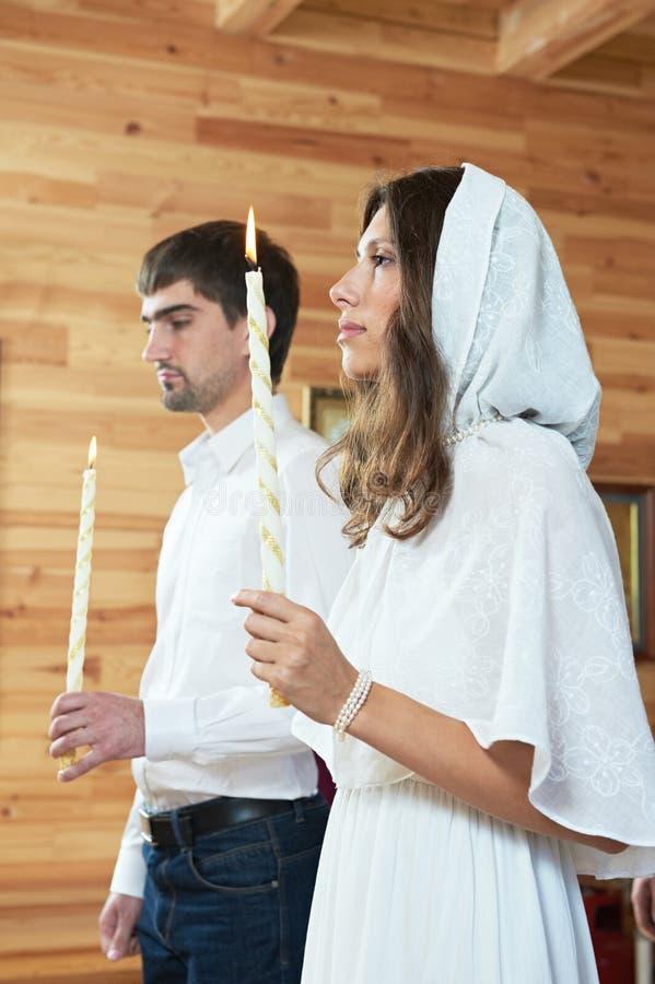 Ortodox bröllopceremoni man och kvinna med stearinljus på kyrkan royaltyfria foton
