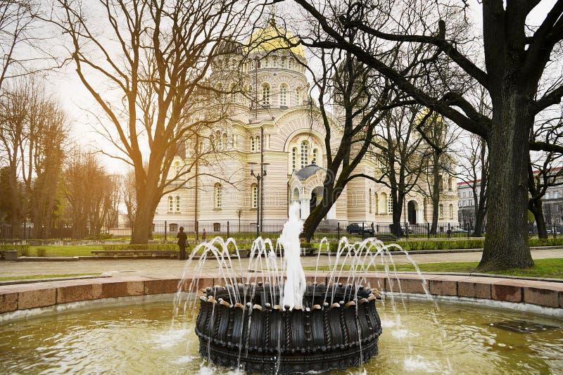 Ortodox Kristi födelse av Kristusdomkyrkan i Riga, Lettland och antik springbrunn i förgrunden royaltyfria foton
