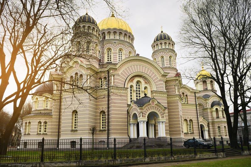 Ortodox Kristi födelse av Kristusdomkyrkan i Riga, Lettland och antik springbrunn i förgrunden royaltyfri fotografi