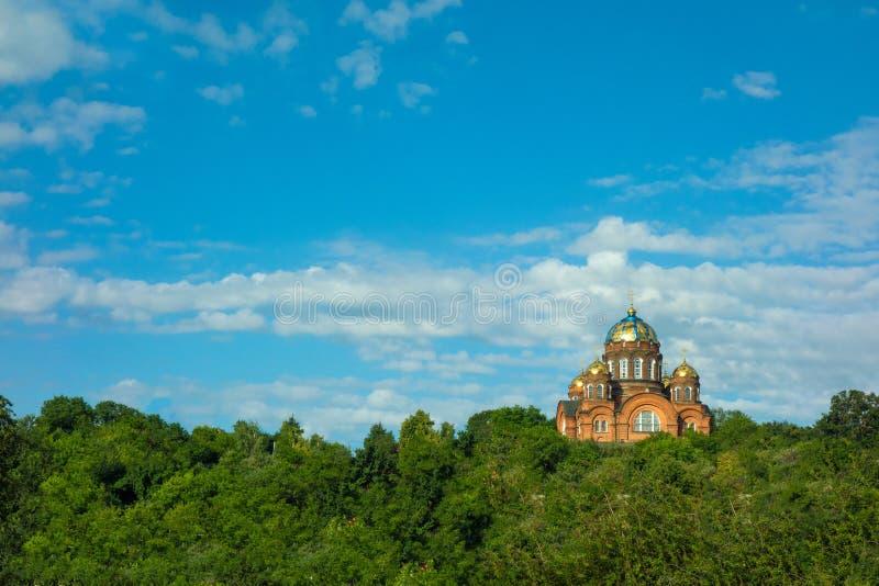 Ortodox kyrka p? en kulle Kristen traditionell tempel på bakgrund av blå himmel för moln och gröna skogträd på den soliga sommard fotografering för bildbyråer