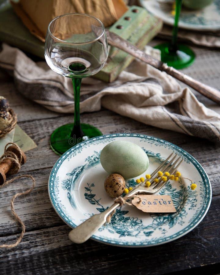Ortodox påsktabellinställning med tappningplattor med den gröna prydnaden, gafflar, färgade ägg, vaktelägg, gul blomma fotografering för bildbyråer
