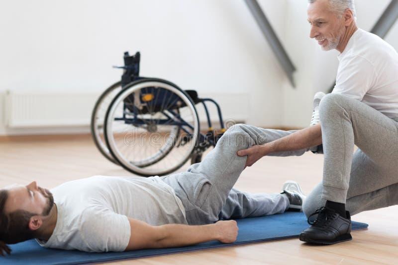 Ortopedico carismatico che allunga gli handicappati nella palestra immagine stock