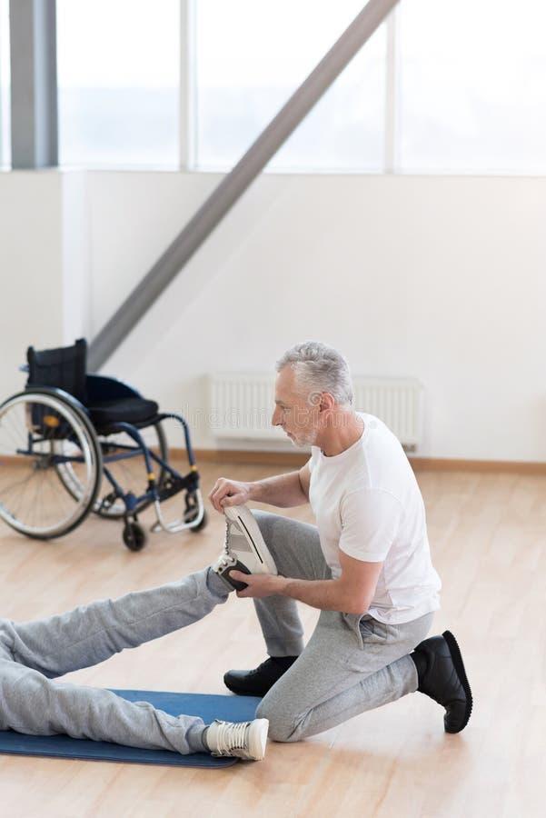 Ortopedico invecchiato attento che aiuta il paziente disabile nella palestra fotografia stock