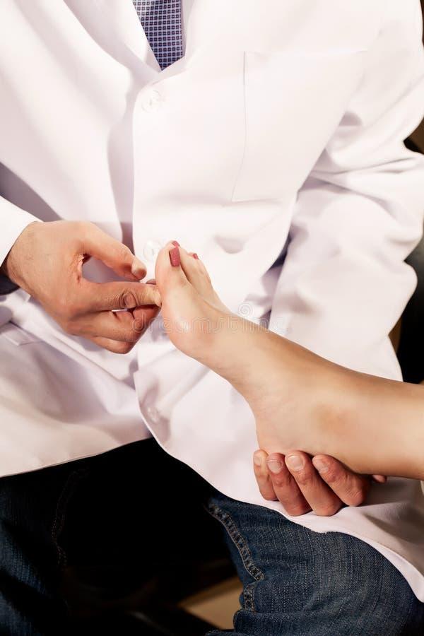Ortopedisk doktor i hans kontor med modellen av foten arkivbild