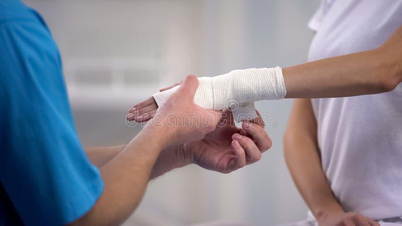 Ortopedista que aplica o envoltório elástico do pulso na deslocação comum da mão paciente fêmea foto de stock