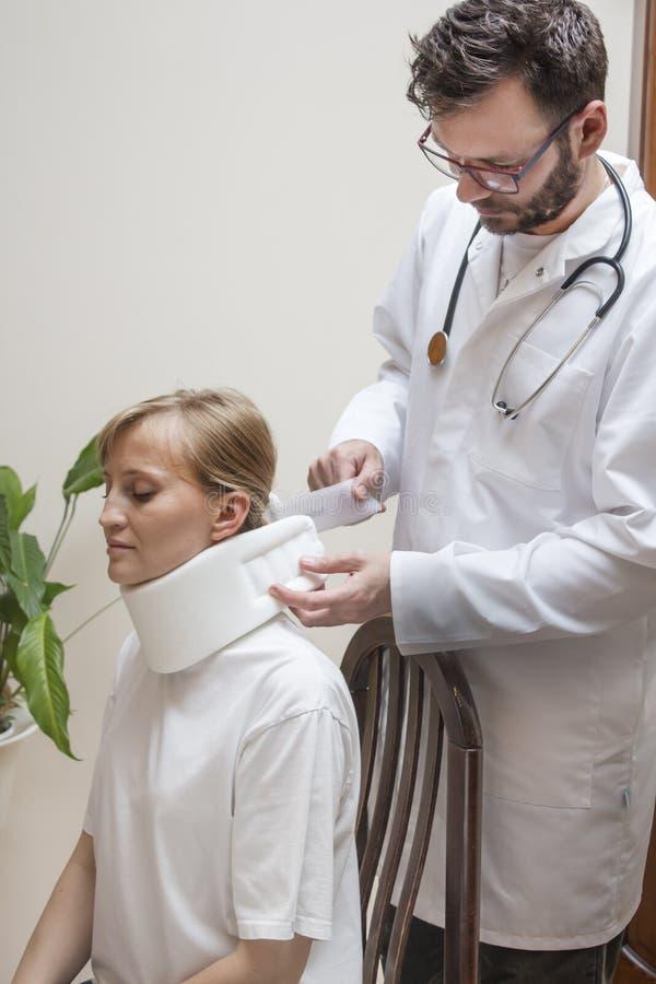 Ortopedyczny chirurg stawia dalej białego ortopedycznego kołnierz młodej kobiety obsiadanie na krześle obraz royalty free