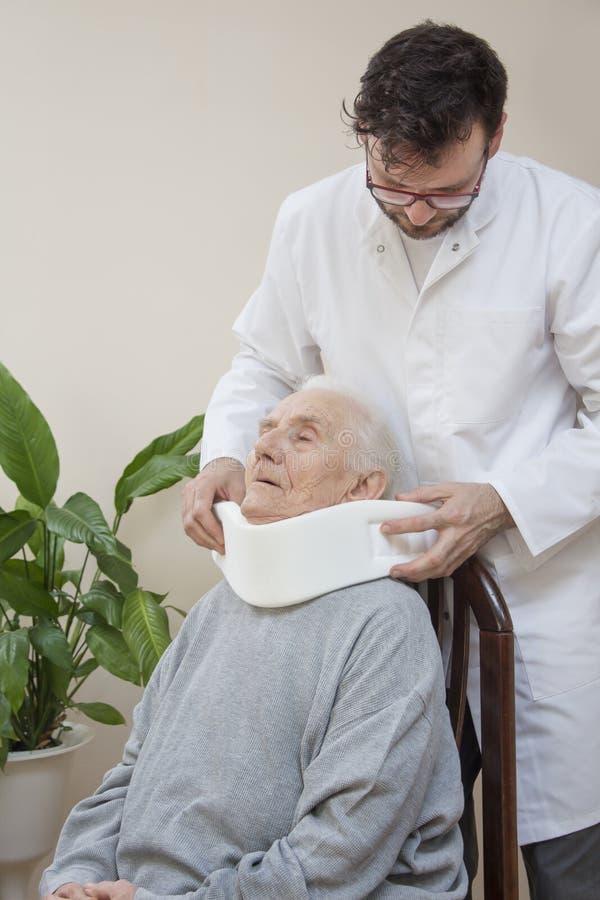 Ortopedyczny chirurg stawia dalej białego ortopedycznego kołnierz prawdziwy starej kobiety obsiadanie na krześle zdjęcia royalty free