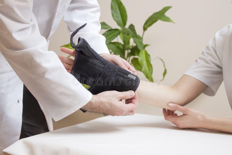 Ortopedyczny lekarz praktykujący zakłada czarnej ręki stabilizator na pacjenta żeńskiej ręce obrazy royalty free